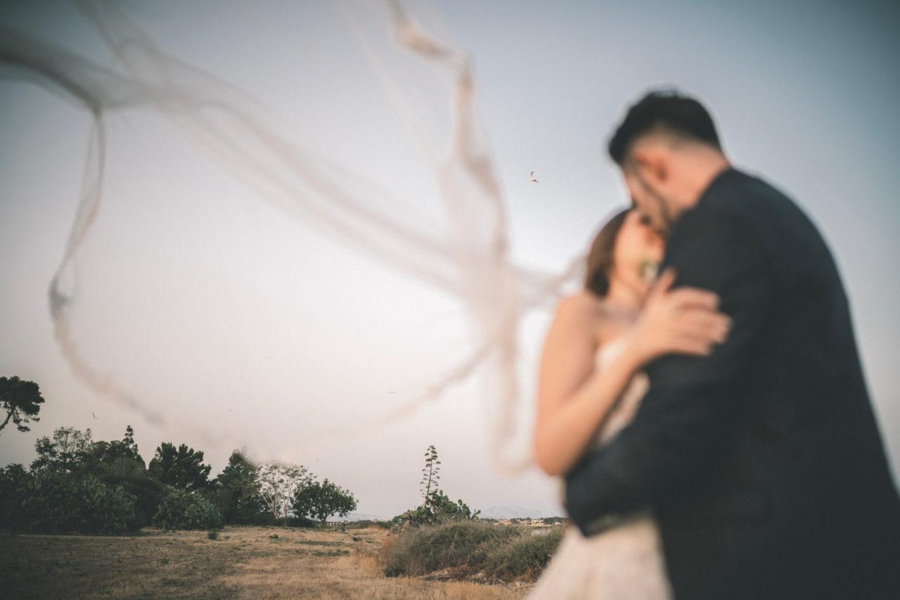 F.A.Q. Wedding Photography - Bacio Sposi con Velo al Vento e gabbiano nello Sfondo